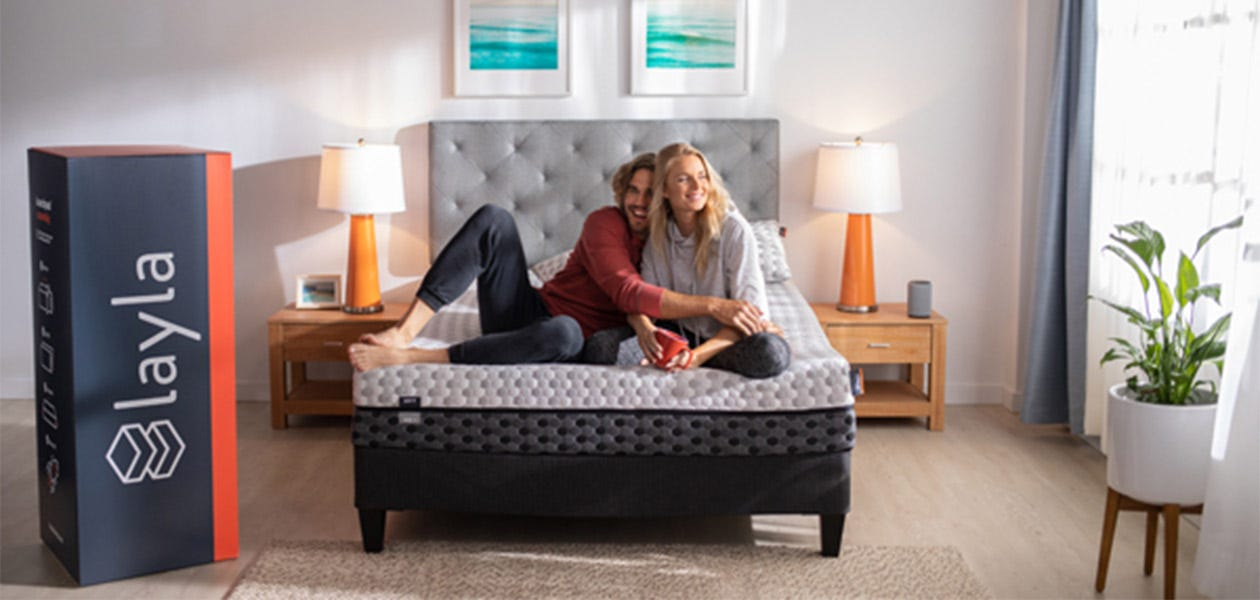 A couple sits together on their new Layla Memory Foam Mattress