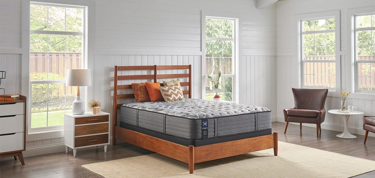 A Posturepedic Plus mattress set up in a room