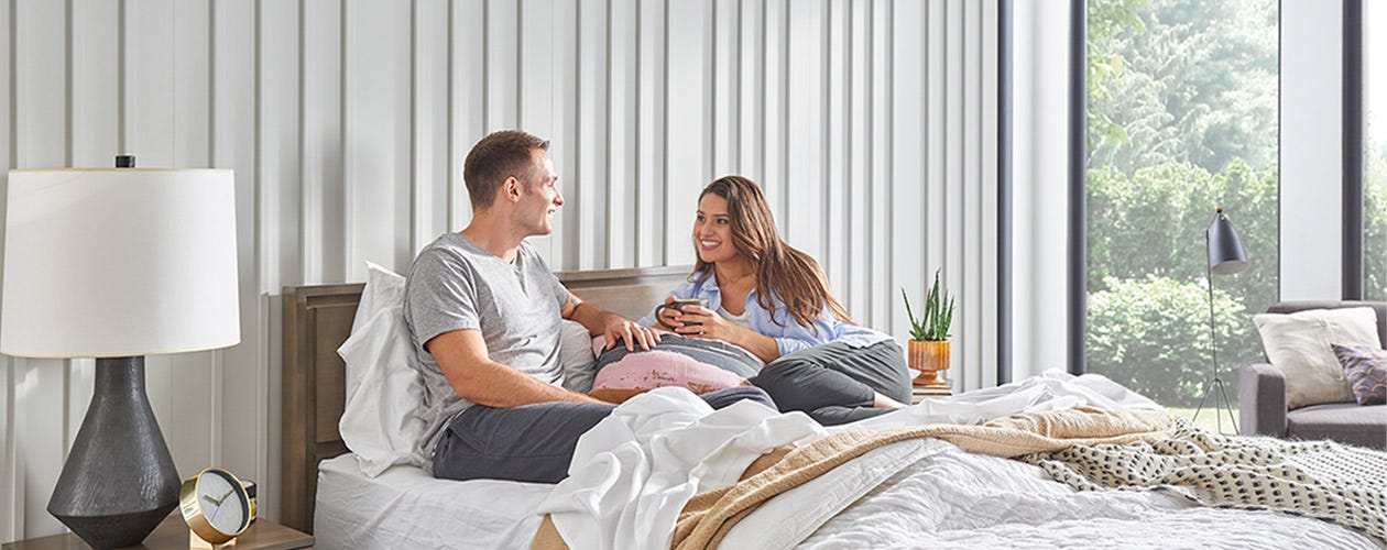 A couple hanging out on a Sealy bed