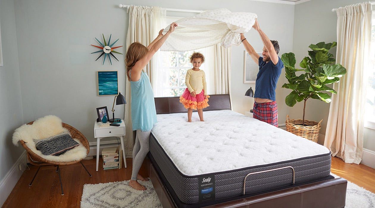 A family puts the sheets on a Sealy Response