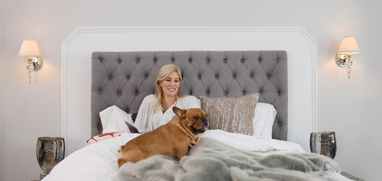 A woman and her dog hanging out on a Stearns & Foster Reserve Collection mattress.