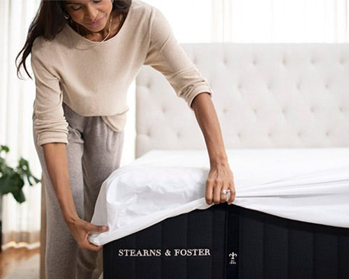 Woman putting sheet on a Stearns & Foster bed