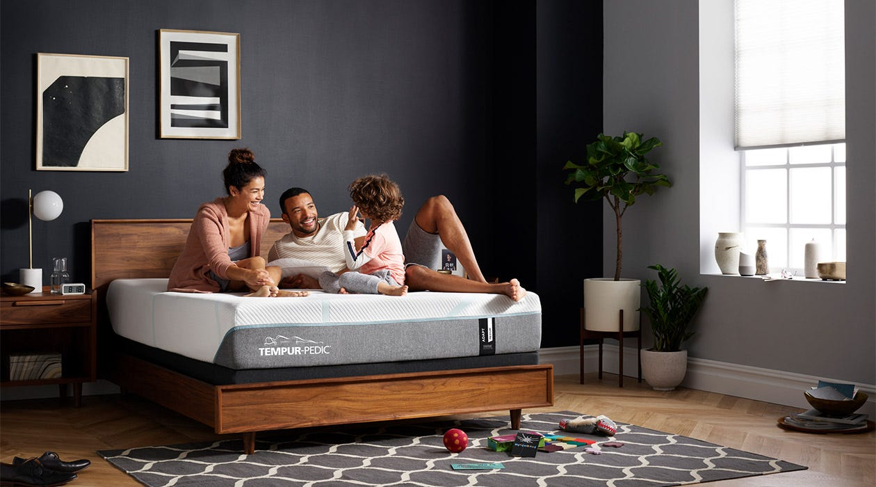 Family laying on an Adapt mattress in gray room