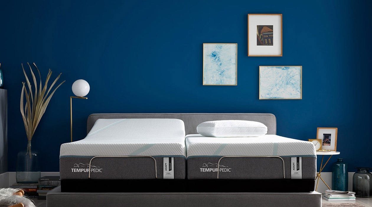 Dark blue room view of an Adapt mattress with split adjustable base