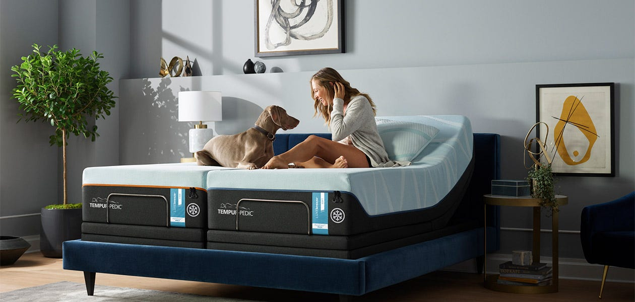 Woman and dog sitting on a slit Luxe Breeze mattress in a room