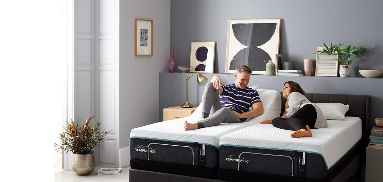 A woman and man lying on a split pro-adapt bed with two different comfort levels