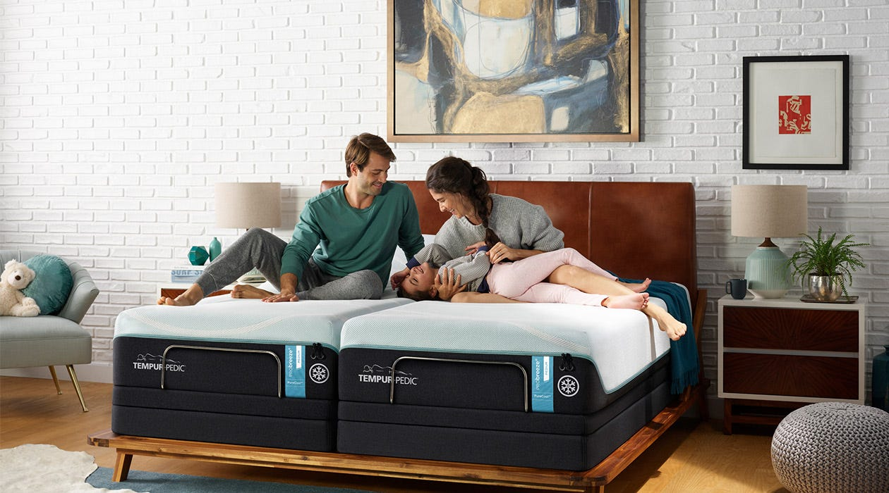 A family plays on a split Pro Breeze bed in a bedroom