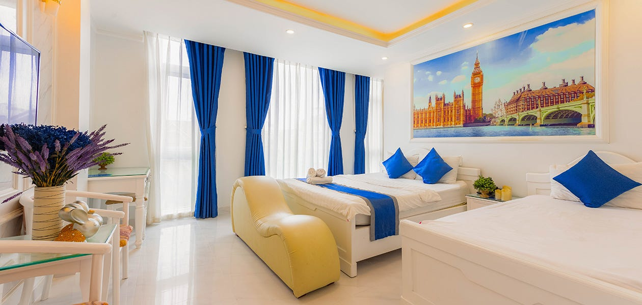 A bright hotel room features two beds with blue accessories